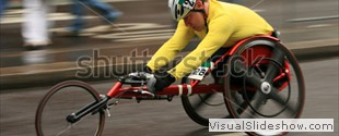 stock-photo-a-fast-moving-wheelchair-athlete-competes-in-a-marathon-with-motion-blur-11484106